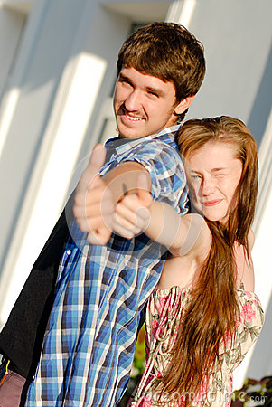 Young happy couple showing thumbs up