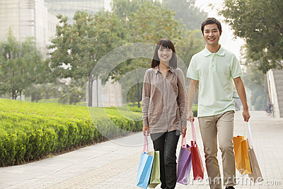 Young happy couple walking with colorful shopping bags in hands in Beijing, China