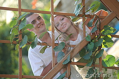 Young happy couple at wooden lattice