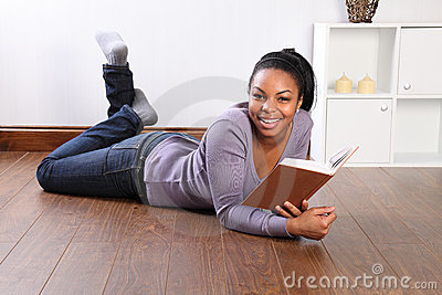 Young happy female student reading book at home