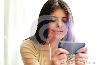 Young happy female student using smartphone