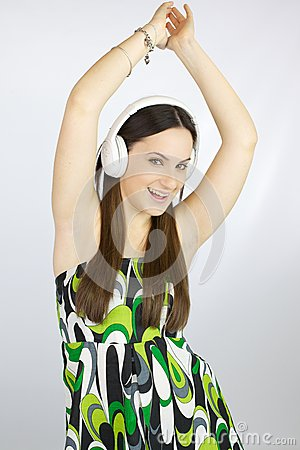 Young happy girl dancing with headphones