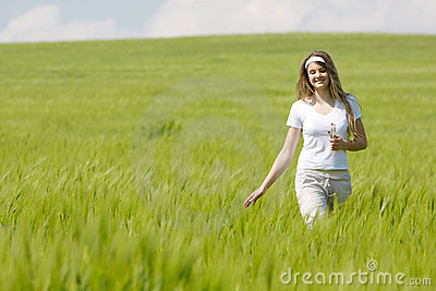 Young happy girl walking in field