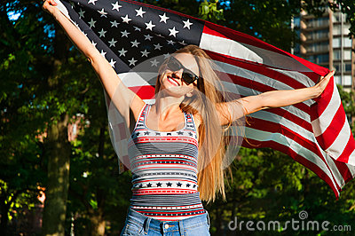 Young happy patriot woman holding the united states flag