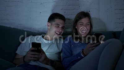 Young happy and romantic couple on their 20s using together mobile phone enjoying sitting at home sofa couch laughing having fun stock video footage
