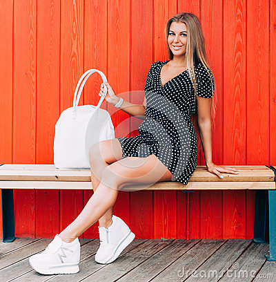 Free Young Happy Smiling Blonde Tan Woman Posing Outdoor In Summer Time Wearing Vintage Dress, Sitting At Wooden Bench At Red Backgroun Stock Images - 95191054