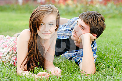 Young happy smiling couple lying outdoors