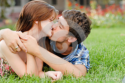 Young happy smiling couple lying outdoors and kiss