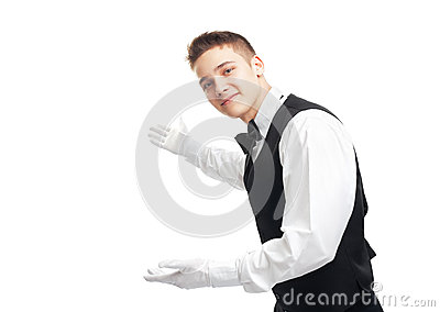 Young happy smiling waiter gesturing welcome