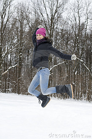 The young happy woman the brunette jumps on snow