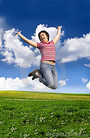 Young happy woman jumping high against blue sky