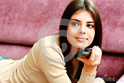 Young happy woman lying on the sofa with remote control