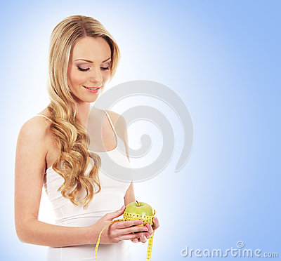 A young and happy woman measuring an apple