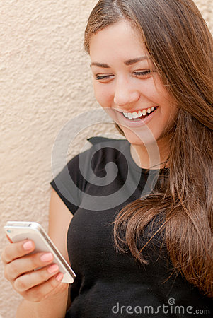 Young happy woman reading message on mobile phone