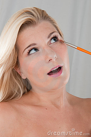 Young healthy woman doing eye make-up with a brush