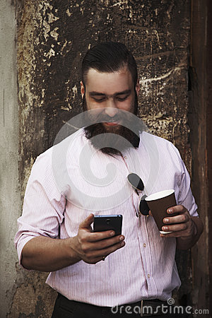 Free Young Hipster Businessman With Beard Holding  Phone And A Coffee Royalty Free Stock Photo - 78906595