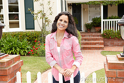 Young Hispanic woman standing outside home