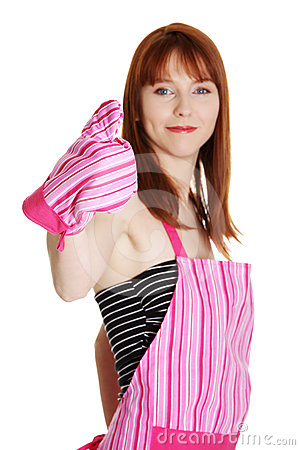 Young housewife in pink apron showing thumbs up