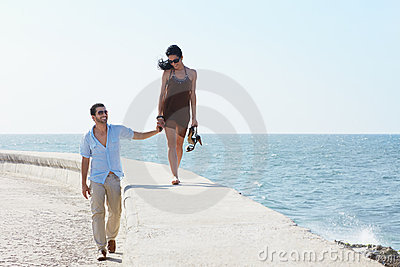 Young husband and wife walking near the sea