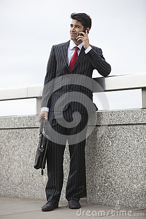 Young Indian businessman using cell phone with laptop bag by parapet