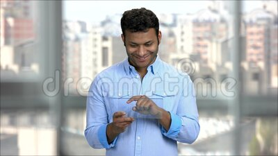 Young Indian man using blank transparent tablet. Portrait of smiling arabic guy swiping on invisible digital device stock video footage