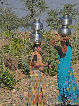 Young Indian women carry pots of water Editorial Stock Photo