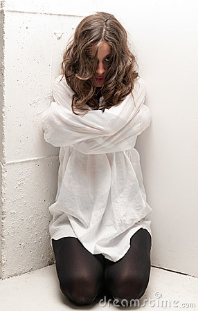 Young insane woman with straitjacket on knees