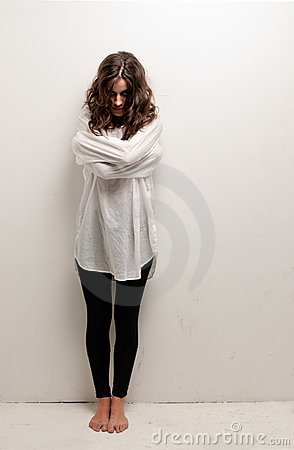 Young insane woman with straitjacket standing