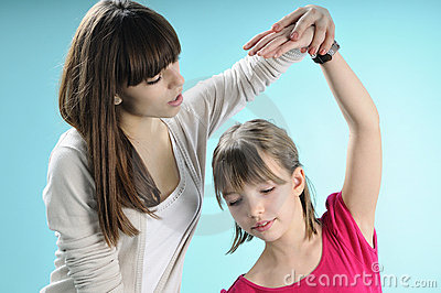 Young instructor and girl exercising ballet