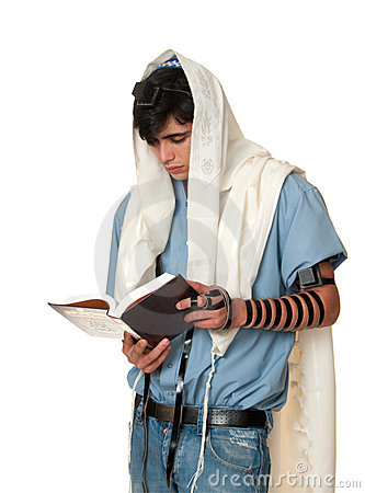 Young jewish man prays wearing tallit and tefillin