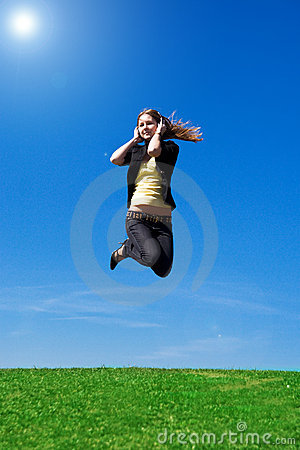 The young jumping girl with headphones