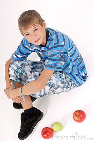 Young kid laying on the floor and 3 apples