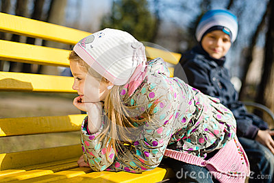 2 young kids pretty girl and boy having fun sitting & playing on a bench in the park on spring or autumn outdoors background