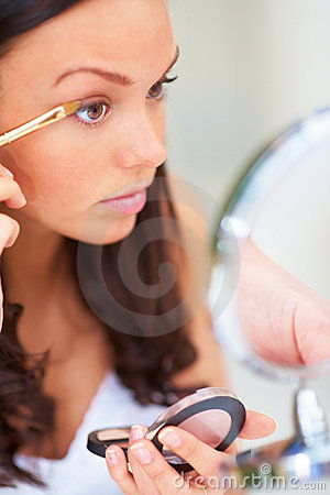 Young lady carefully applying makeup