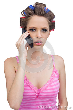 Young lady in hair curlers having a phone call