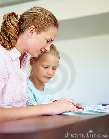 A young lady helping her daughter doing homework