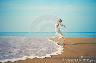 Young lady jumping on the beach