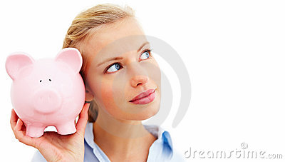 Young lady listening for coins in her piggy bank