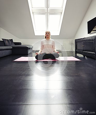 Young lady practicing yoga in her living room