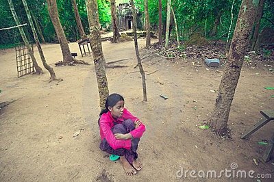 Young lady sitting on the ground inside of Ta Som Editorial Photography