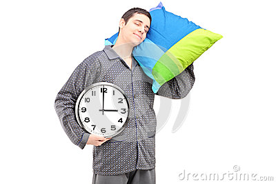 A young lazy guy holding a wall clock and sleeping on a pillow