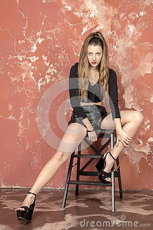 Free Young Long-haired Long-legged Skinny Girl In A Black Sweater And Leather Shorts And Platform Sandals Royalty Free Stock Image - 57091986