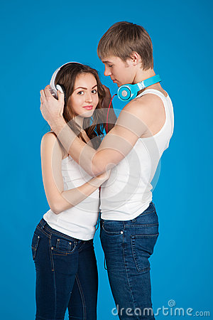 Young love couple. Boy putting on headphones, listening music in