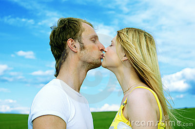 Young love couple kiss in field