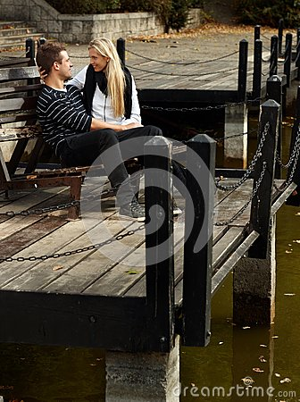 Young loving couple in park by lake