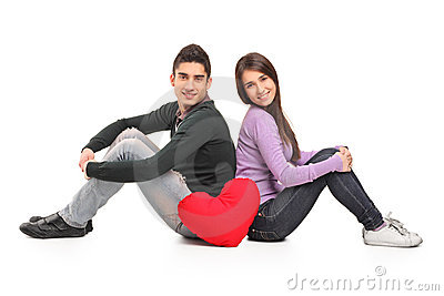 Young loving couple and a red heart shaped pillow