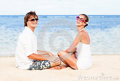 Young loving couple in white on tropical beach.