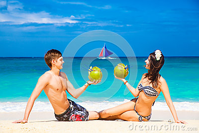 Young loving happy couple on tropical beach, with coconuts