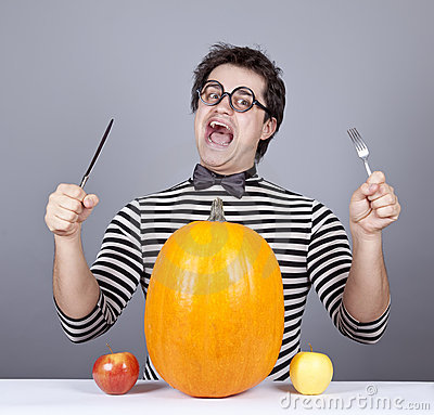 The young mad men try to eat apples and pumpkin.