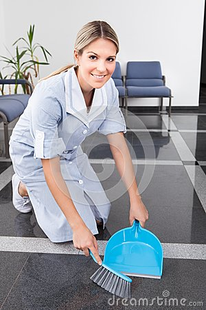Young maid sweeping the floor